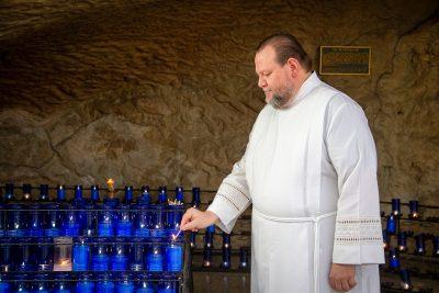 Fr. David P. Uribe, O.M.I. lighting candles at the Grotto